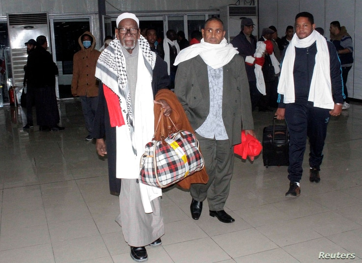 Some of the 111 passengers from a plane that was hijacked and diverted to Malta walk through Tripoli's Mitiga International Airport, Libya, Dec. 24, 2016.
