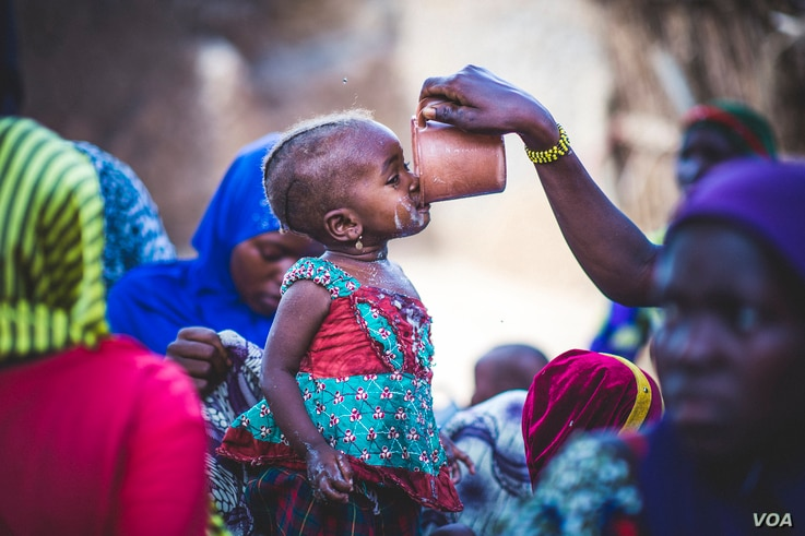 A toddler samples millet porridge after a cooking demonstration in Zinder, Niger, Aug. 31, 2016. (Sean Sheridan photo courtesy of Mercy Corps)