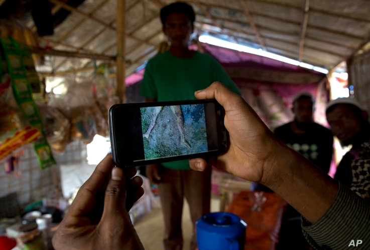 Rohingya Muslim refugee Mohammad Karim, 26, shows a mobile video of Gu Dar Pyin's massacre inside his kiosk in Kutupalong refugee camp, Bangladesh, Jan. 14, 2018.