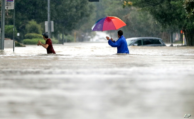 Moses Juarez, left, and Anselmo Padilla wade through floodwaters from Tropical Storm Harvey, Aug. 27, 2017, in Houston, Texas.