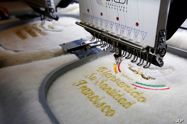 An embroidery machine gives the last touches to a ruana, a traditional Colombian garment, that will be given to Pope Francis during his upcoming visit to Colombia, in Nobsa, Colombia,  Aug. 25, 2017.