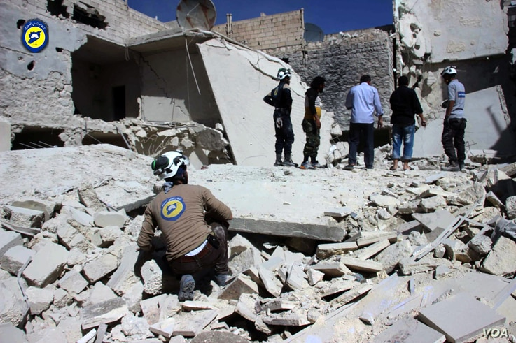 Mideast Syria: This photo provided by the Syrian Civil Defense group known as the White Helmets, shows members of Civil Defense inspecting damaged buildings after airstrikes hit the Bustan al-Qasr neighborhood of Aleppo, Syria, Sunday, Sept. 25, 2016...