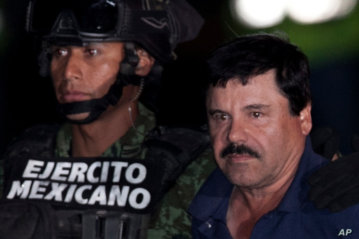 """Mexican drug lord Joaquin """"El Chapo"""" Guzman, right, is escorted by soldiers and marines to a waiting helicopter, at a federal hangar in Mexico City, Jan. 8, 2016."""