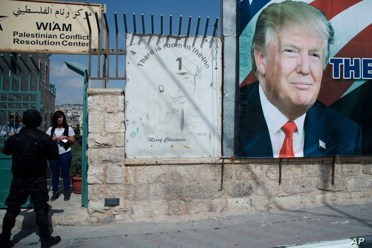 A woman watches a motorcade carrying President Donald Trump to a meeting with Palestinian President Mahmoud Abbas,  May 23, 2017, in the West Bank City of Bethlehem.