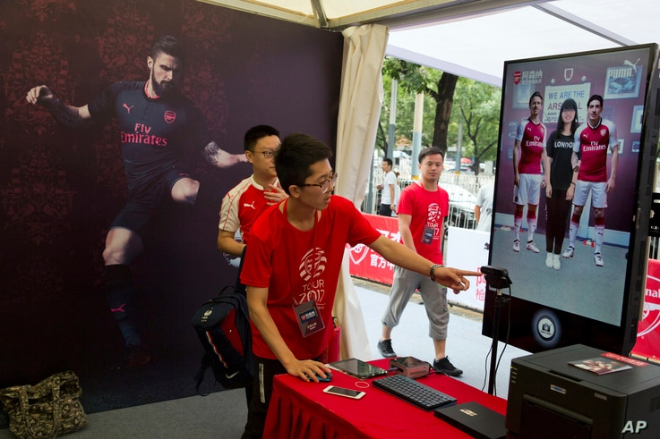 FILE - A worker directs a fan of Arsenal into position for an augmented reality photo session during an exhibition ahead of an Arsenal vs. Chelsea soccer match in Beijing, China, July 21, 2017.