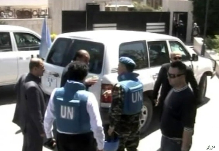 This image made from video made available by Syrian TV shows United Nations observers during a visit to Homs, Syria, April 21, 2012.