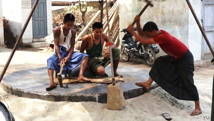 Workers build one of the giant gongs at a workshop in Myanmar that will later go to a temple or monastery. (Z. Aung/VOA)