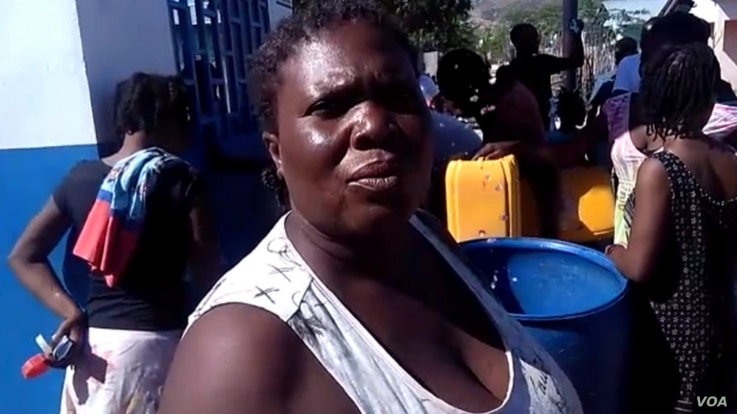 This woman told VOA Creole she's been back to the water kiosk three times today and is grateful to have access to fresh water in Gonaives, northern Haiti. (Photo: Exalus Mergenat / VOA Creole)