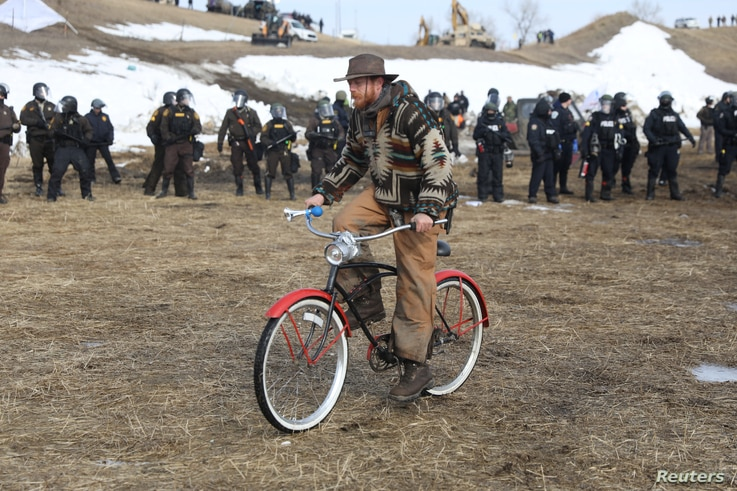 A man rides a bicycle away from the police as they attempt to clear the Oceti Sakowin camp, Feb. 23, 2017.