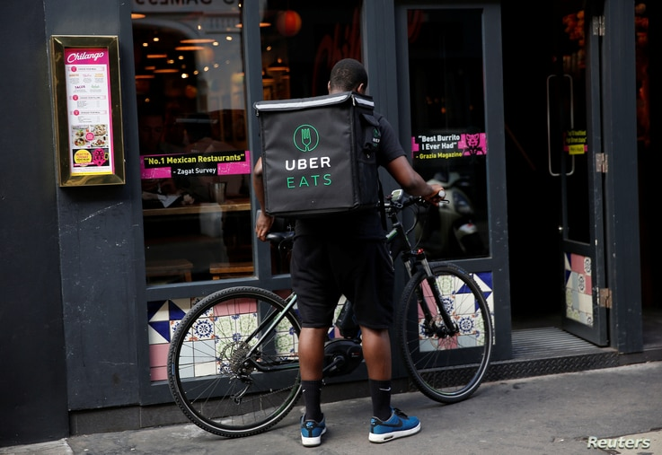 An UberEATS food delivery courier prepares his bike in London on September 7, 2016. Uber is advertising to fill jobs from general managers to bike couriers.