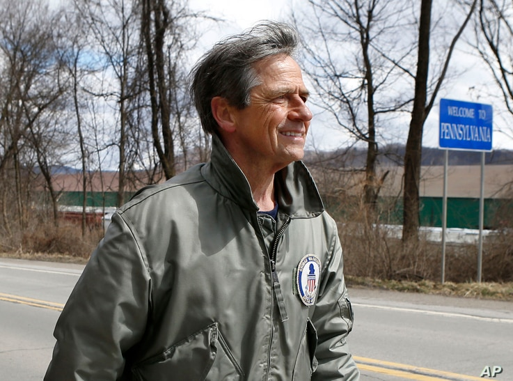 """FILE - In this March 28, 2015 photo, Joe Sestak, a candidate seeking the Democratic Party nomination for the US Senate, passes a sign for the border between Pennsylvania and Ohio as he completes his """"Walking In Other Pennsylvanian's Shoes,"""" a walking..."""