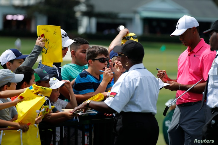 Tiger Woods of the U.S., right, signs autographs before his practice round for the 2018 Masters golf tournament at Augusta National Golf Club in Augusta, Georgia, April 2, 2018.