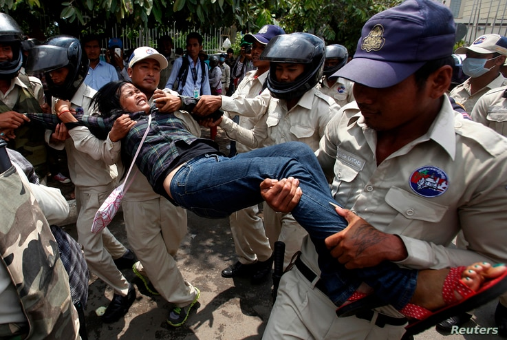 FILE - Cambodian security officers carry off a woman during a protest near the National Assembly in Phnom Penh, Aug. 27, 2014. Boeung Kak Lake residents and other communities who are embroiled in land disputes gathered to appeal for help from the gov...