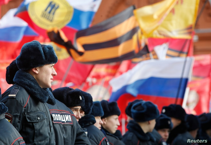"""Policemen stand in front of participants of an """"Anti-Maidan"""" rally against the 2014 Kiev uprising, which ousted President Viktor Yanukovich, in Moscow, Feb. 21, 2015."""