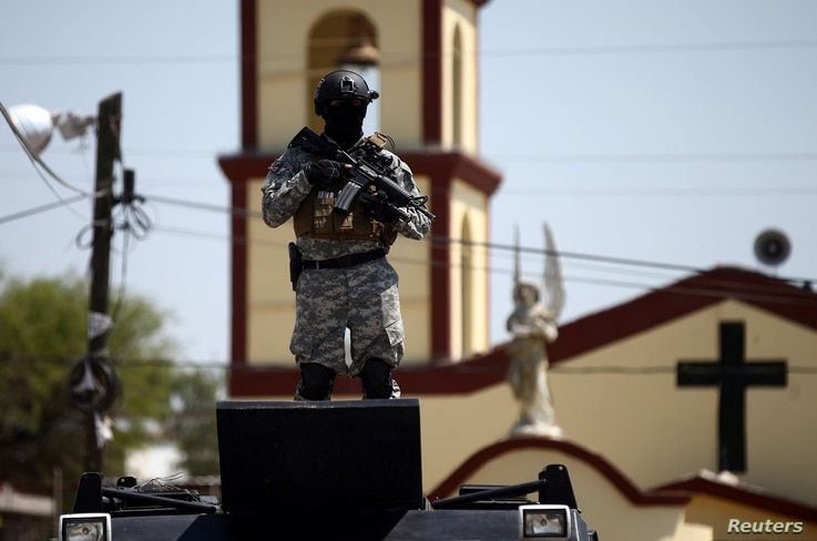 A soldier stands guard after a blockade set by members of the Santa Rosa de Lima Cartel to repel security forces during an anti-fuel theft operation in Santa Rosa de Lima, in Guanajuato state, Mexico, March 6, 2019.