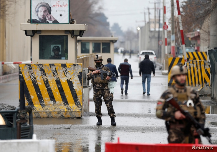 Afghan security forces keep watch at a check point near the site of a suicide attack in Kabul, Afghanistan, Feb. 24, 2018.