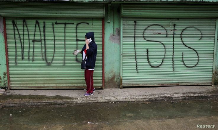 """FILE - A man is seen using a mobile phone while passing a shuttered store front with """"MAUTE-ISIS"""" graffiti, in Marawi city, southern Philippines, Oct. 20, 2017. Maute, an Islamic State affiliate, was among groups the U.S. added to its terror list Tue..."""