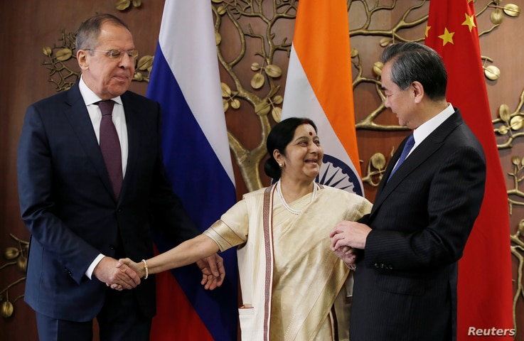 Russian Foreign Minister Sergei Lavrov (L) Indian Foreign Minister Sushma Swaraj  (C) and Chinese Foreign Minister Wang Yi shake hands before the start of their meeting in New Delhi, India, Dec. 11, 2017.