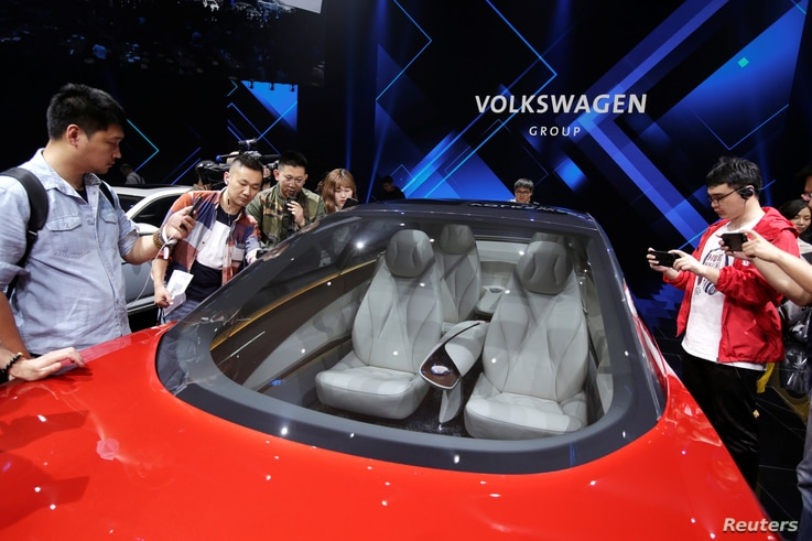 Journalists visit a Volkswagen I.D. concept car at a media event ahead of the Beijing Auto Show in Beijing, China April 24, 2018.