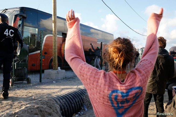 "A volunteer waves to migrant minors in a bus during their transfer by French authorities to reception centers across the country at the end of the dismantlement of the camp called ""the Jungle"" in Calais, France, Nov. 2, 2016."