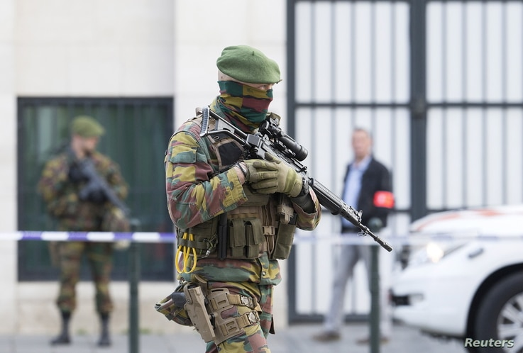 A Belgian special forces police officer and soldiers secure the zone outside a courthouse while Brussels attacks suspects Mohamed Abrini and Osama Krayem appear before a judge, in Brussels, Belgium, April 14, 2016.