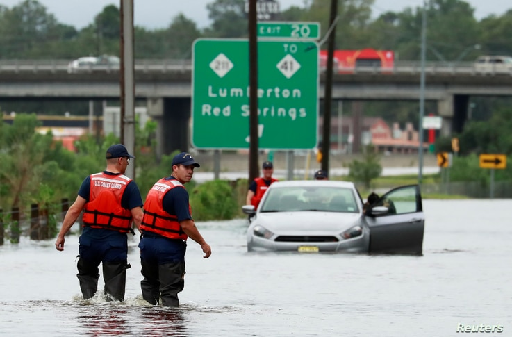 Members of the Coast Guard help a stranded motorist in the flood waters caused by Hurricane Florence in Lumberton, North Carolina, Sept. 16, 2018.