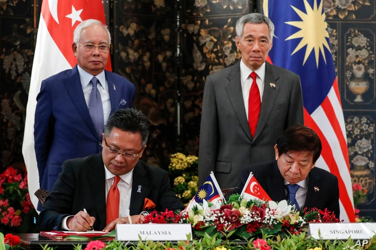 Malaysia's Prime Minister Najib Razak, and Singapore's PM Lee Hsien Loong, witness the signing of an agreement on the Johor Bahru-Singapore Rapid Transit System Link at the Istana or presidential palace in Singapore, Jan. 16, 2018.