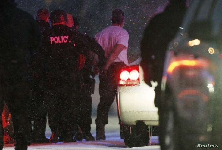 Police put the man suspected of killing at least three people during a shooting at a Planned Parenthood center in Colorado Springs, Colorado into a police vehicle, Nov. 27, 2015.