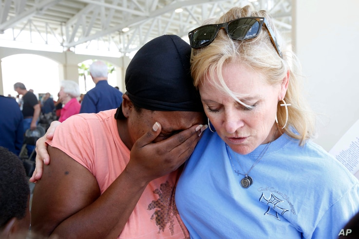 April Moore of Gulfport, left, cries after thanking Anne Warren of Gulf Coast Blessings for prayers from her Bible group following a Katrina 10 Year Remembrance in Gulfport, Miss., Aug. 29, 2015.