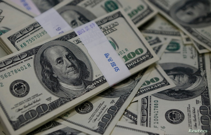 U.S. one-hundred dollar bills are shown,  Aug. 2, 2013.  Almost 20 people were arrested March 1, 2017, as authorities put an end to a complex international fraud and money laundering ring.