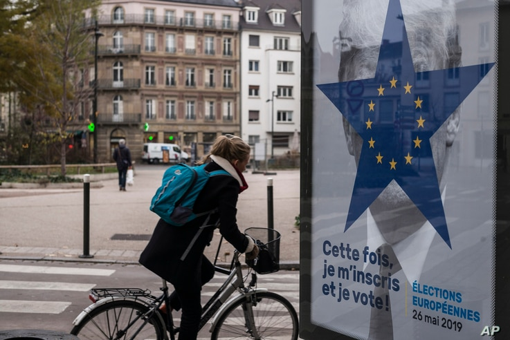 A cyclist rides past of campaign poster by the Strasbourg municipality for the upcoming European elections in Strasbourg, eastern France, Nov. 22, 2018.