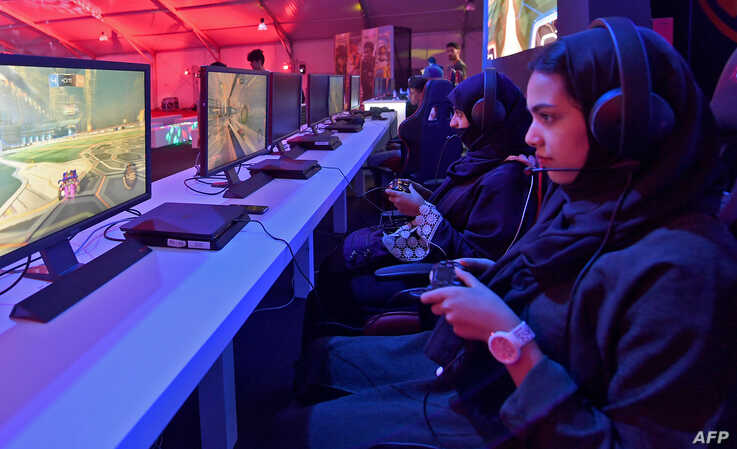 FILE - Saudi youths play at an electronic entertainment house accessible to men and women in Jeddah, Saudi Arabia, May 15, 2019.