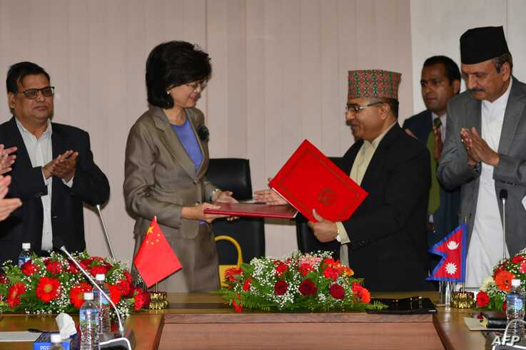 Nepal's Foreign Secretary Shankar Das Bairagi and China's Ambassador to Nepal Yu Hong, second from left, exchange documents during a signing ceremony relating to the One Belt One Road initiative in Kathmandu, May 12, 2017.