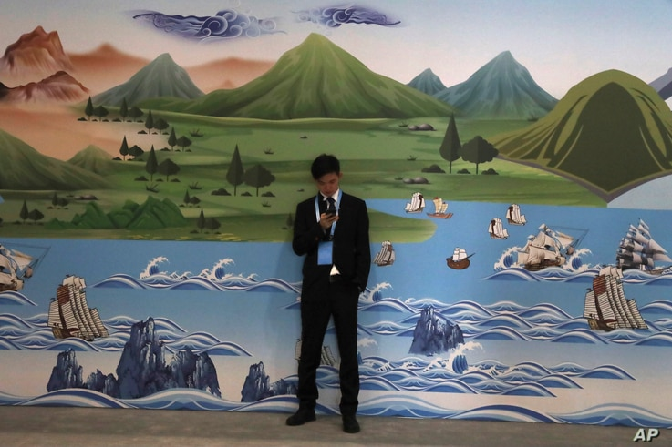 A man stands near a mural depicting the ancient Silk Road during the Second Belt and Road Forum in Beijing, April 26, 2019.