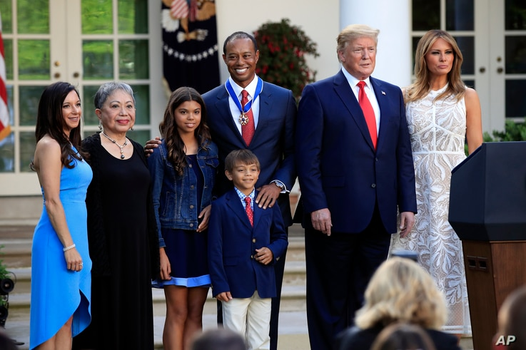 President Donald Trump, first lady Melania Trump and Tiger Woods pose for a picture with, from left, Woods' girlfriend Erica Herman, his mother Kultida Woods, children Sam Alexis Woods and Charlie Axel Woods, May 6, 2019.