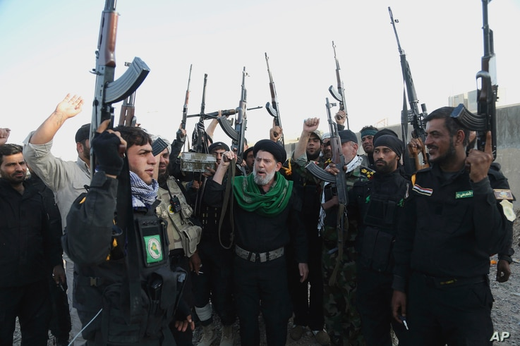 FILE - Iraqi Shiite militia group called Imam Ali Brigades chant slogans against the Islamic State group at the battlefield in Tikrit, 130 kilometers (80 miles) north of Baghdad, Iraq, March 14, 2015.