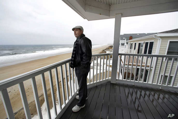 Real estate agent Tom Saab stands on a oceanfront deck at a condo he developed in Salisbury, Mass., Feb. 15, 2019. Academic researchers say concerns over rising sea levels and increased flooding are having subtle but significant impacts on coastal pr...