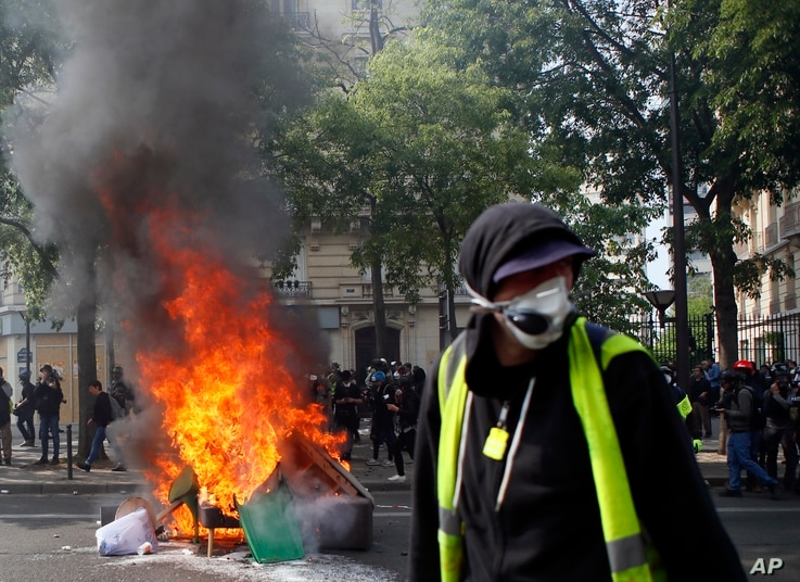 A man walks past garbage that was set on fire in Paris, May 1, 2019. Brief scuffles between police and protesters broke out in Paris as thousands of people gathered for May Day rallies under tight security measures.