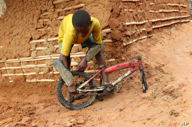 A young boy inspects part of a bicycle retrieved from a site where two houses were crushed by the collapse of a massive, sprawling dumpsite in Pemba city on the northeastern coast of Mozambique, Monday, April, 29, 2019.