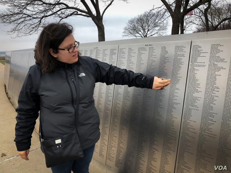 Erin Josen points to the name of a great-grandparent who immigrated to the U.S., inscribed on Ellis Island's American Immigrant Wall of Honor. (R. Taylor/VOA)
