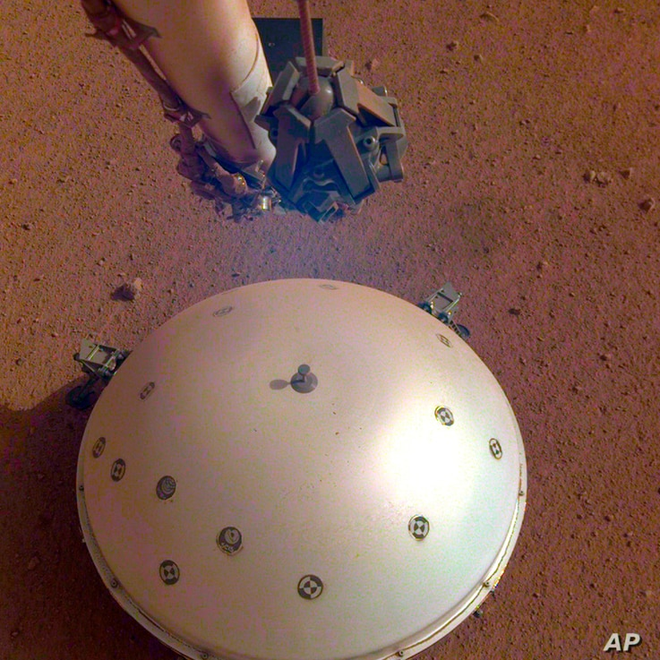 This photo made available by NASA, April 23, 2019 shows the InSight lander's domed wind and thermal shield which covers a seismometer on the 110th Martian day, or sol, of the mission.