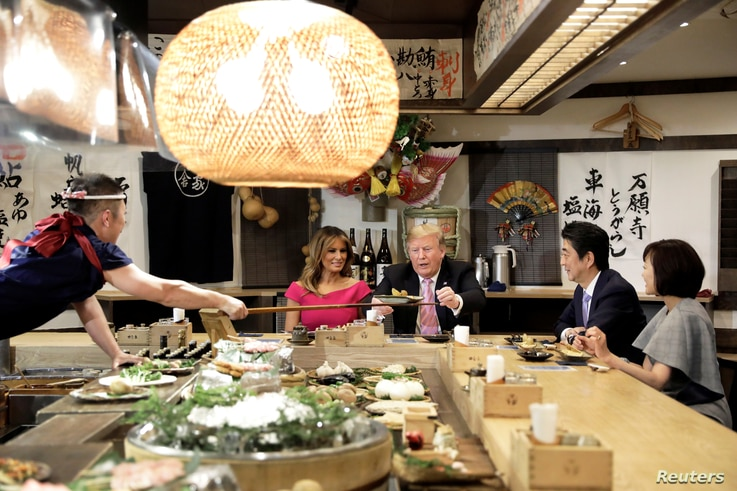 U.S. President Donald Trump, with first lady Melania Trump, receives a plate of food from a chef as they and Japanese Prime Minister Shinzo Abe and his wife Akie Abe have a couples dinner in Tokyo, May 26, 2019.