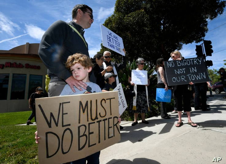 Kyle Fox, 4, and his father Brady Fox hold a sign at a vigil held to support the victims of Chabad of Poway synagogue shooting, April 28, 2019, in Poway, Calif.
