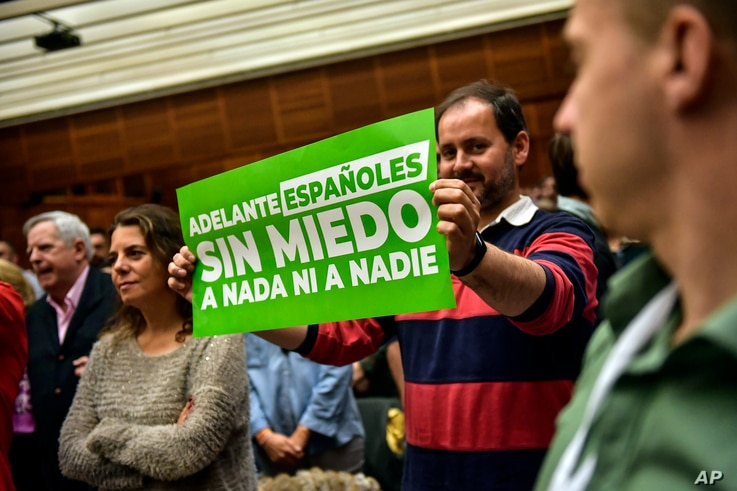 FILE - A supporter of Santiago Abascal, leader of Spanish far-right party Vox, shows a banner reading ''Spaniards, Forward. Without fear of anything or anyone,'' during a campaign meeting in San Sebastian, northern Spain, April 13, 2019.