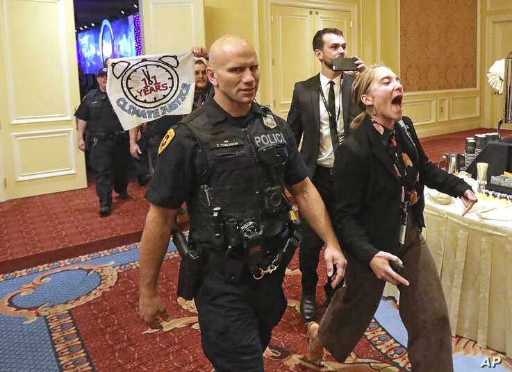 About 25 protesters are escorted by police after interrupting a energy summit where U.S. Energy Secretary Rick Perry spoke, May 30, 2019, in Salt Lake City. Perry says the Trump administration is committed to making fossil fuels cleaner rather than i...