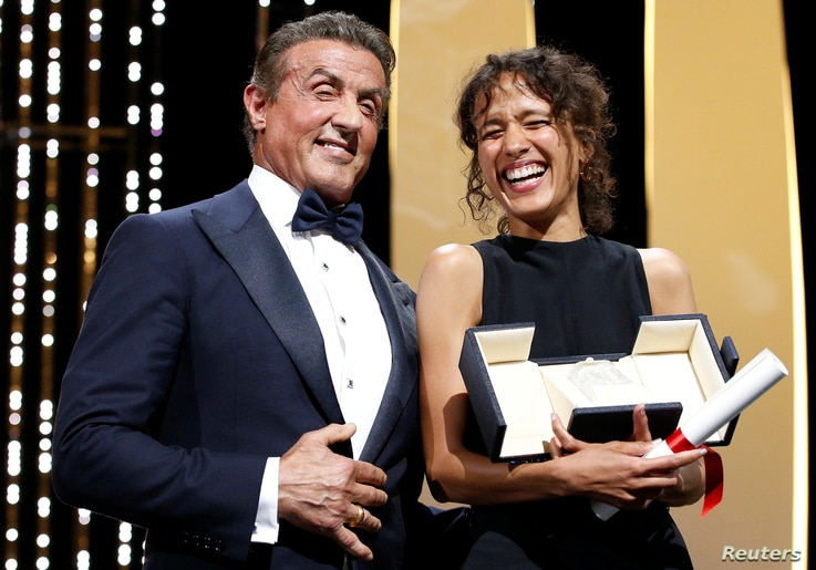 """Director Mati Diop, Grand Prix award winner for her film """"Atlantics,"""" reacts next to Sylvester Stallone at the 72nd Cannes Film Festival in Cannes, France, May 25, 2019."""