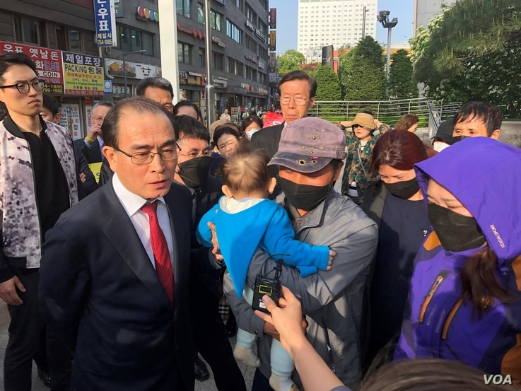 Thae Yong Ho, a former North Korean diplomat, translates for the family of a nine-year-old girl who was detained in China. (B. Gallo/VOA)