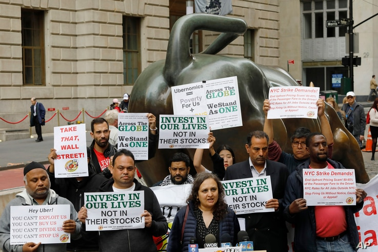 Uber drivers protest next to the Charging Bull statue in New York's financial district, May 8, 2019. The protests arrive just ahead of Uber's initial public stock offering, which is planned for May 10, 2119.