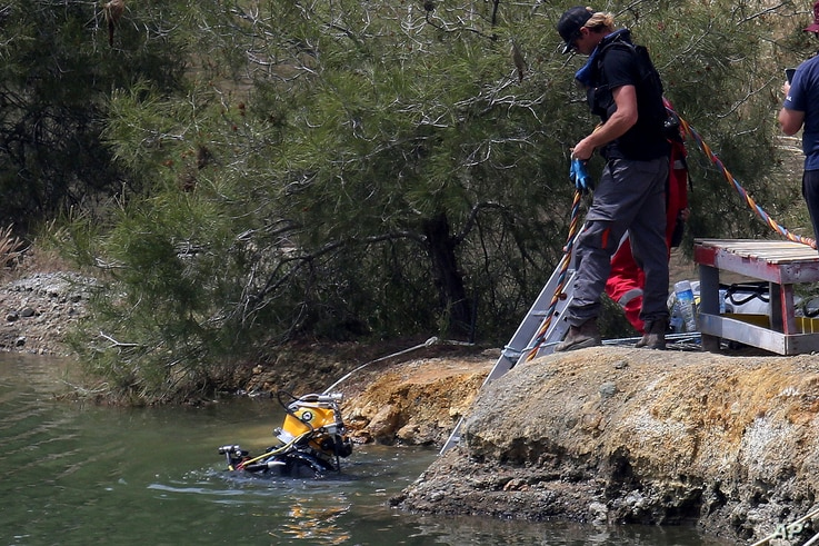 A diver enters a lake to search for female bodies near the village of Xiliatos outside of Nicosia, Cyprus, April 26, 2019. Cyprus police are intensifying a search for the remains of more victims at locations.