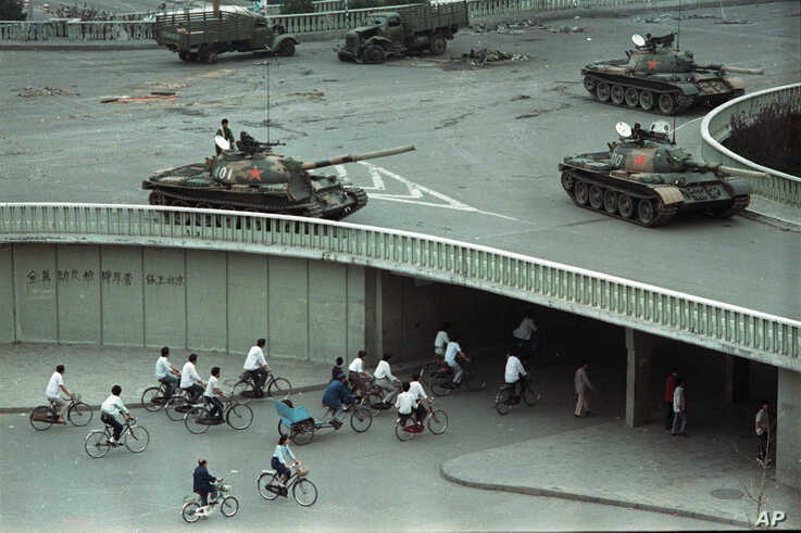 Bicycle commuters, sparse in numbers, pass through a tunnel as above on the overpass military tanks are positioned in Beijing, China, two days after the Tiananmen Square massacre,on Tuesday morning, June 6, 1989.